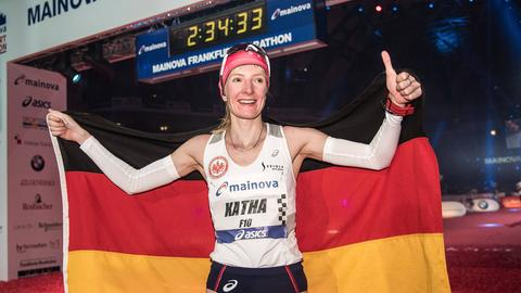 Katharina Heinig feiert mit der deutsche Fahne im Ziel.