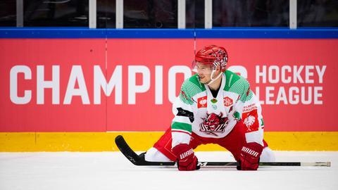 Mark Richardson kniet auf dem Eis und lächelt.