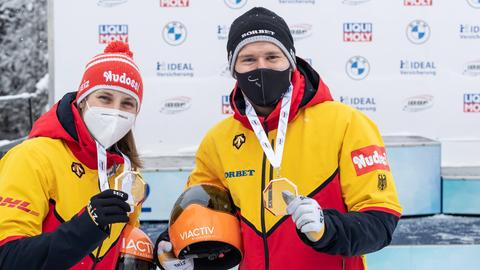 Die Skeletonis Tina Hermann und Christopher Grotheer halten ihre Goldmedaillen in die Höhe