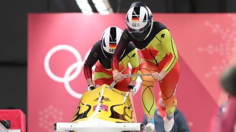 Anna Köhler und Erline Nolte schieben den Bob an.