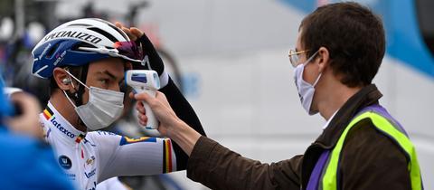 Ein Profi-Radsporlter bei einer Fieber-Thermometer-Kontrolle