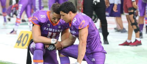 Zwei Spieler der Frankfurt Universe knien und beten gemeinsam.