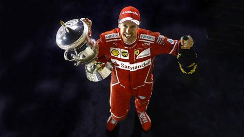 Vettel mit Pokal und Schampusflasche