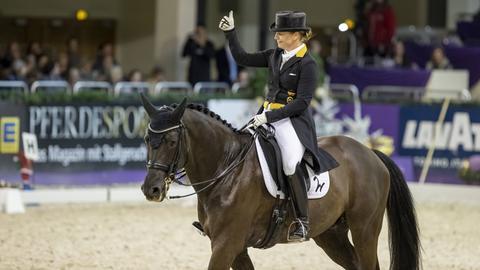 Isabell Werth sitzt auf dem Pferd und streckt den Daumen hoch.