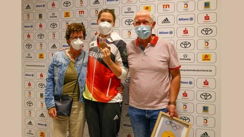 Sarah Köhler mit ihren Eltern am Flughafen - Papa Köhler hält das Gold-Geschenk an seine Tochter in der Hand