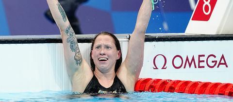 Sarah Köhler befindet sich am Rand des Schwimmbecken, reißt die Arme hoch und hat einen sehr freudigen Gesichtsausdruck..