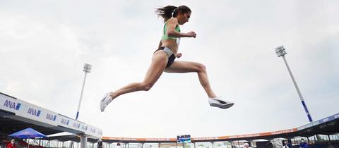 Gesa Krause in Leichtathletikwettkampfkleidung springend in der Luft - aus der Froschperspektive fotografiert.