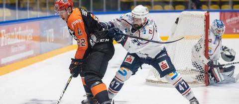 Eduard Lewandowski von den Löwen Frankfurt und Derek Dinger von den Kassel Huskies liefern sich einen Zweikampf.