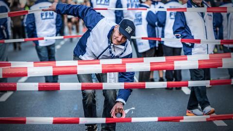 Ein Helfer montiert für den Marathon eine Sperre.
