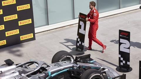 """Ein wütender Sebastian Vettel schnappt sich nach dem Rennen die Nummerntafel mit der """"1"""", die vor Lewis Hamiltons Auto stand."""