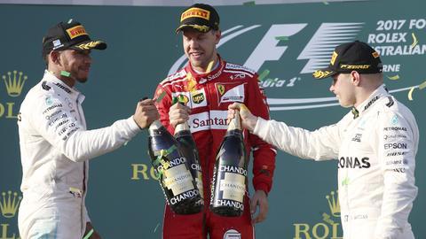 Anstoßen auf den Formel-1-Start: Siegerehrung in Melbourne mit Sieger Vettel, Hamilton (li.) und Bottas (re.).