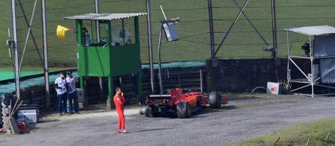 Ein ziemlich einsamer Sebastian Vettel steht neben seinem ramponierten Ferrari.