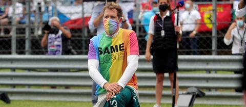 Vettel kniet vor dem GP in einem Regenbogen-Shirt
