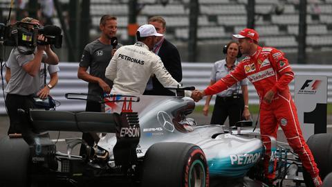 Sebastian Vettel gibt Lewis Hamilton die Hand.