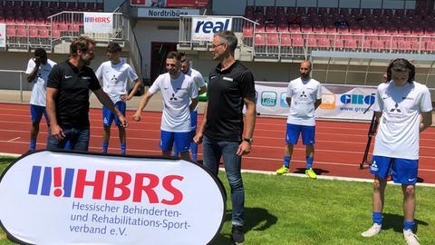 Uwe Bindewald beim angedeuteten Fistbump mit einem Spieler von der Fußballmannschaft, daneben Alexander Schur.