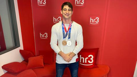 Eduard Trippel vor einer hr3-Wand mit seinen Medaillen