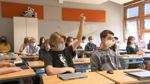 Schüler meldet sich in Klasse.