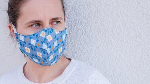 Eine Frau trägt einen selbstgemachten Mundschutz mit Blümchenmuster.