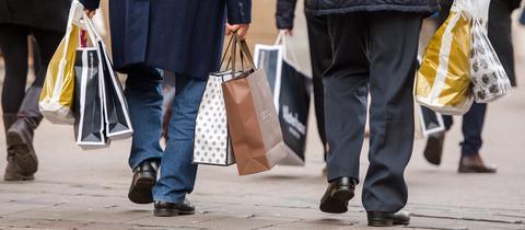 Menschen mit Einkaufstüten auf Straße.