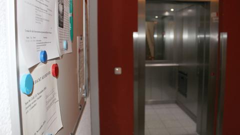Eine Pinnwand für Notizen der Hausbewohner und der Aufzug des Hauses