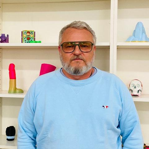 Ein Mann in einem blauen Pulli steht vor einem Regal. In dem Regal liegen viele Kunstskulpturen.
