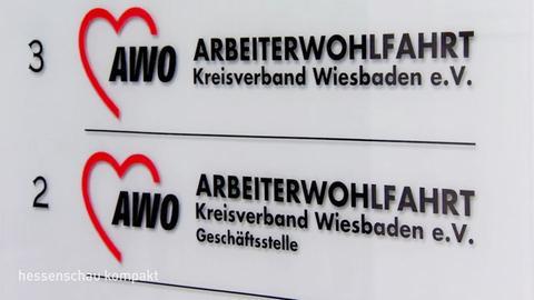 """Das Foto zeigt ein Schild mit der Aufschrift """"AWO Kreisverband Wiesbaden e.V."""" wie es an Hauseingängen zu finden ist."""