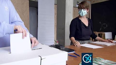 An einem Tisch stehen zwei Personen: eine steckt einen Zettel in eine  Wahlurne aus Karton, eine andere steht daneben und schaut zu. Auf den Tisch liegen viele Papiere.