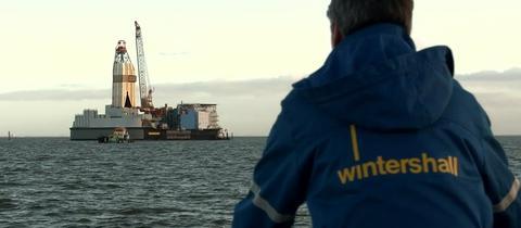 Wintershall-Mitarbeiter vor einem Öl- und Gasförderturm