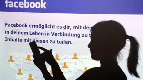 Eine Frau tippt auf dem Smartphone, im Hintergrund ist eine Facebook-Optik zu sehen