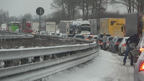 Eine lange Kolonne von Fahrzeugen steht im Stau auf der A7 in Osthessen nach einem erneuten Wintereinbruch mit viel Schneefall.