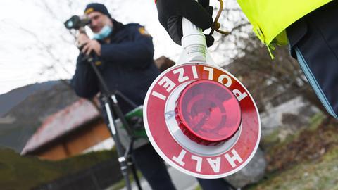 Mann mit Radarmessgerät 'Halt Polizei' Kelle im Vordergrund