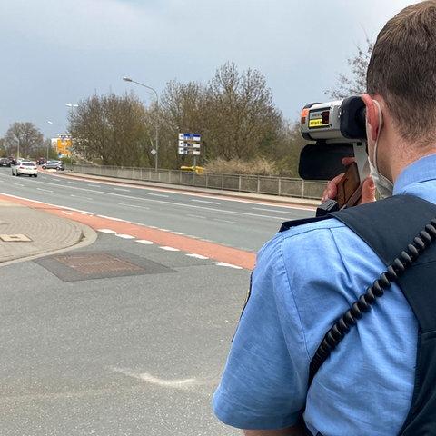 Polizist mit Rücken zum Betrachter und Radarmessgerät an Strasse