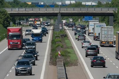 Autos auf der Landstraße, am Bildrand ein Baustamm mit Unfallspuren