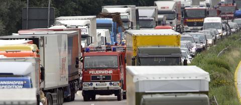 Feuerwehrfahrzeuge fahren auf einer Autobahn durch eine enge Rettungsgasse zu einer Unfallstelle.