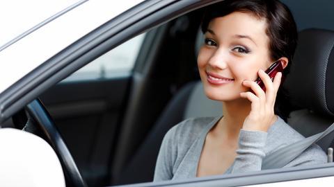 EIne Frau telefoniert im parkenden Auto mit ihrem Handy