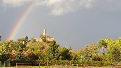 Sonnenbeschienenen Burg vor grauem Himmel mit Regenbogen