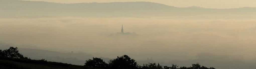 Nur der Kirchturm ragt aus dem Nebel