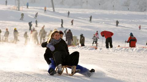 Zwei Frauen rodeln im nordhessischen Willingen einen Hang hinunter.