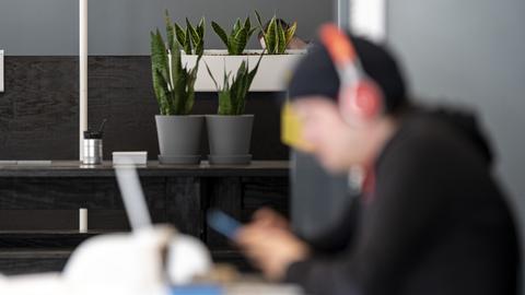 Mensch sitzt verschwommen an Schreibtisch mit Kopfhörern und Handy