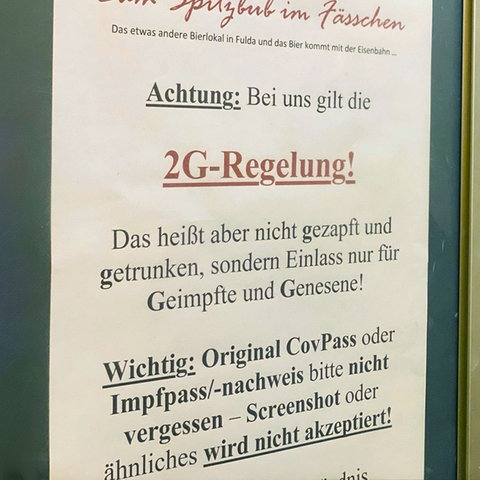 """Foto von einem Zettel, der an der Eingangstür zu einer Kneipe hängt und worauf steht: """"Achtung: Bei uns gilt die 2G-Regel!""""."""