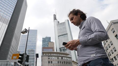 hr-Reporter Marcel Sommer steht zwischen Hochhäusern im Frankfurter Bankenviertel