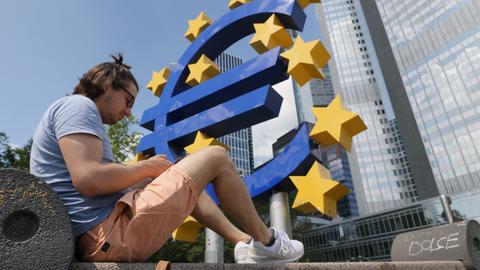 hr-Reporter Marcel Sommer sitzt auf einer Bank, dahinter eine meterhohe Skulptur in Form eines Eurozeichens