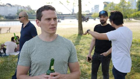 Ein Mann steht mit einer Bierflasche in der Hand an einem Flussufer, hinter ihm drei weitere Männer im Gespräch