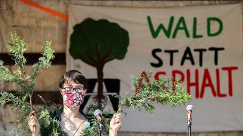 """Eine Demonstrantin neben einem Transparent mit der Aufschrift """"Wald statt Asphalt"""""""