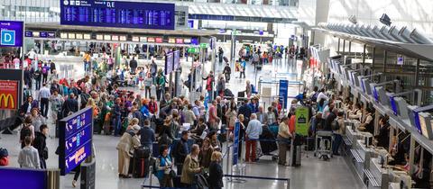 Passagiere stehen an Schaltern im Terminal 2 des Frankfurter Flughafens Schlange.