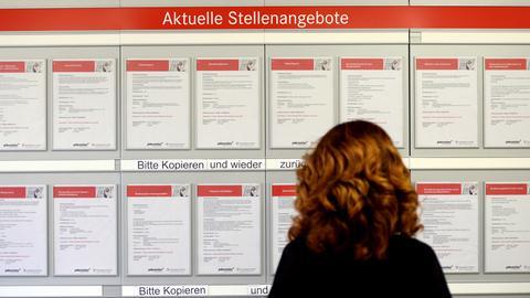 Eine Frau steht vor einer Zettelwand mit Stellenangeboten.