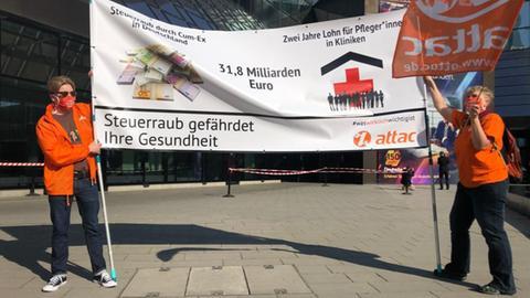 """Demonstranten von Attac halten vor der Deutsche-Bank-Zentrale ein Plakat hoch mit Aufschrift """"31,8 Milliarden Euro - Steuerraub gefährdet ihre Gesundheit"""""""