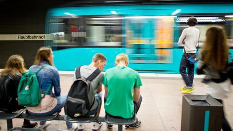 Menschen warten in der U-Bahnstation vom Frankfurter Hauptbahnhof auf die passende U-Bahn.