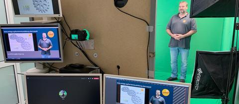Foto- und Filmstudio mit vielen Screens und einer Kamera. Im Hintergrund der eigentliche Studioraum mit einem so genannten green screen und einem Sprecher, der darin für einen Film aufgenommen wird.
