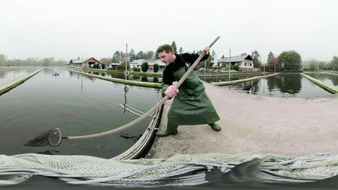 Ein junger Mann, der aus einem Fischzuchtbecken Fische heraushebt. Das Bild können wir mit einer Virtuell Reality-Brille sehen. So ist es verzerrt und hat zwei Fluchtpunkte.